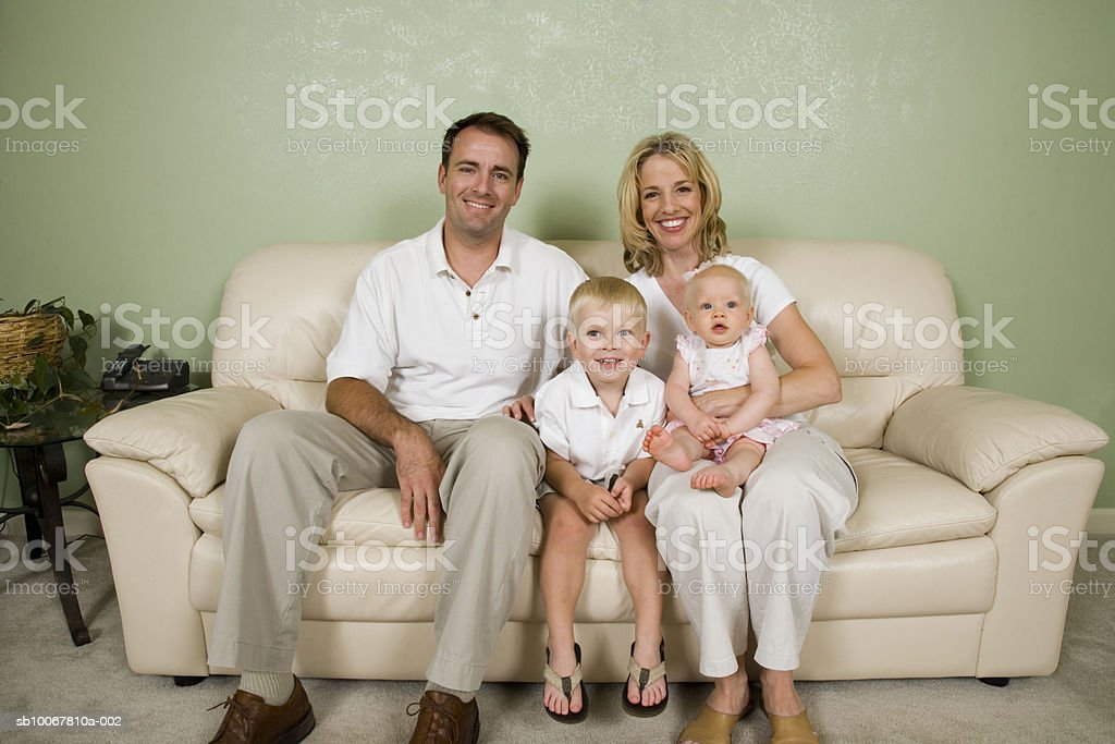 Portrait of family with daughter (9 months) and son (4 years) on sofa royalty free stockfoto