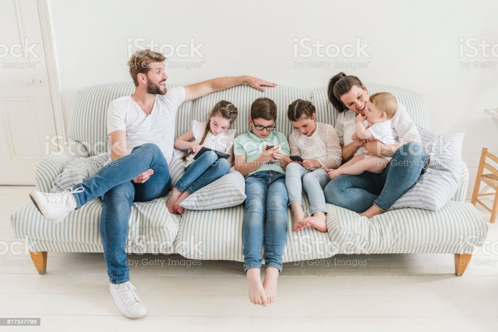 Portrait of family with four children at home on sofa, kids using devices stock photo