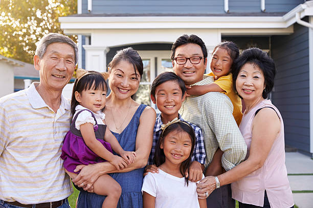 Portrait Of Family With Grandparents Standing Outside House Portrait Of Family With Grandparents Standing Outside House korean ethnicity stock pictures, royalty-free photos & images