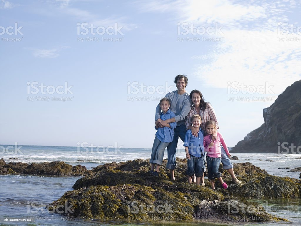 Portrait of family with three children (6-9) at seashore royalty-free stock photo