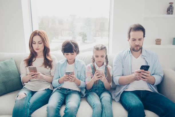 ritratto di famiglia con due bambini che tengono in mano smartphone con dispositivi elettronici in mano sms utilizzando il contatto di ricerca e-mail wi-fi 3g per il controllo dell'internet. concetto di app - assuefazione foto e immagini stock
