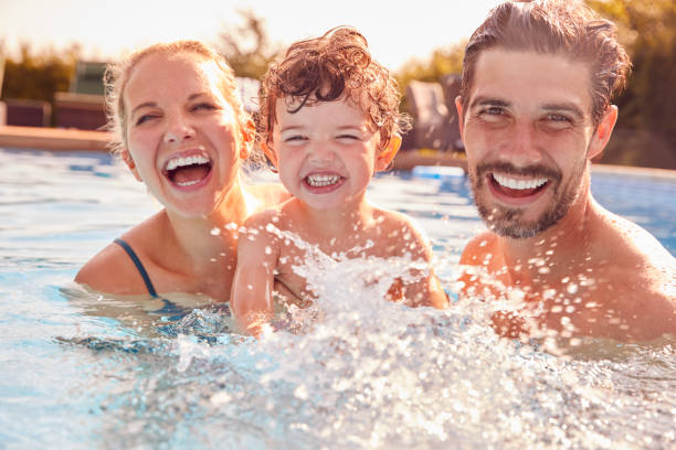 Portrait Of Family With Young Son Having Fun On Summer Vacation Splashing In Outdoor Swimming Pool stock photo