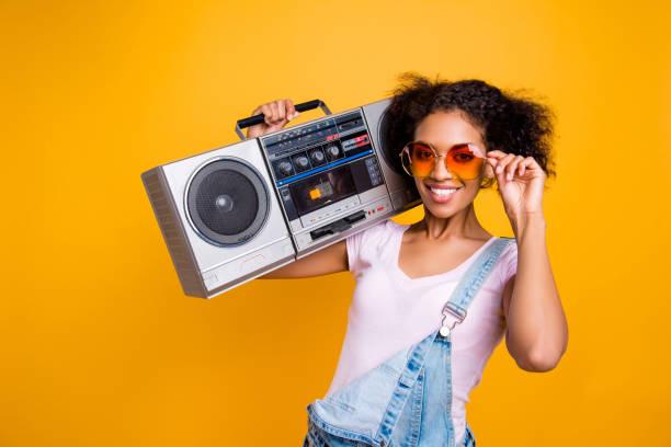 porträt von ausgefallenen toothy mädchen mit strahlenden lächeln in brillen boom-box auf schulter blick in die kamera auf gelbem hintergrund isoliert halten. musik-liebhaber ventilator hobby konzept - radio kultur stock-fotos und bilder