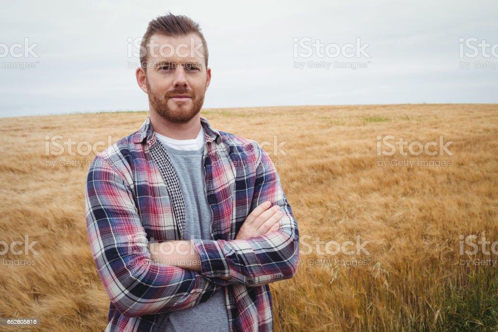 Portrait d'agriculteur debout avec les bras croisés dans le domaine - Photo