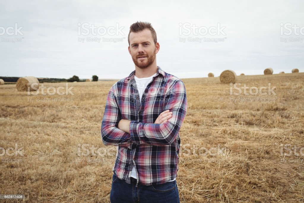 Portrait of farmer standing with arms crossed in the field stock photo