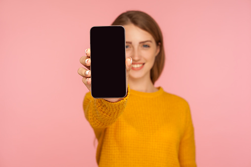 Portrait of fascinating happy ginger girl in sweater showing cellphone to camera and smiling, pleased satisfied with device and application, focus on mobile phone. indoor studio shot pink background