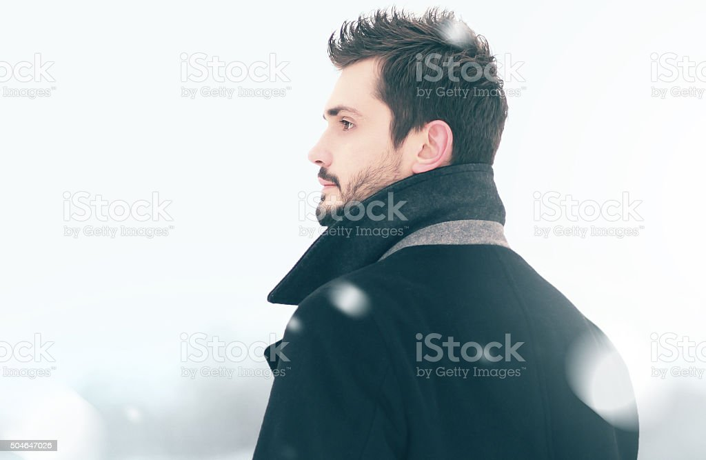 Portrait of fashion handsome man in winter snowstorm looks into stock photo