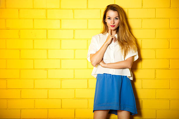 Portrait of Fashion Hipster Girl at the Yellow Wall stock photo