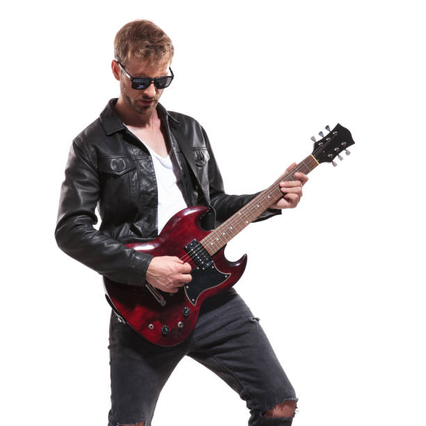 portrait of fashion man playing his electric guitar portrait of fashion man wearing leather jacket and sunglasses playing his electric guitar while standing on white background and looking down guitarist stock pictures, royalty-free photos & images