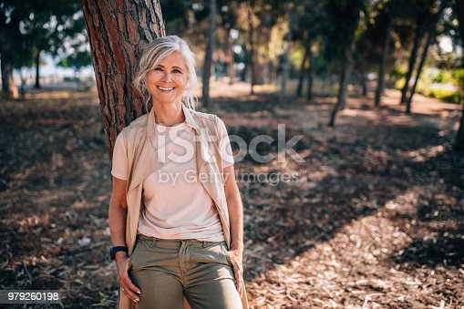 Portrait of beautiful smiling fashionable mature woman standing under tree in forest park in summer