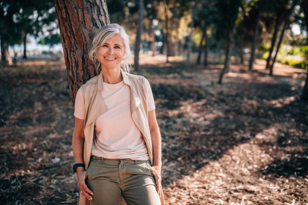 portrait of fashionable senior woman with gray hair in nature - woman portrait forest foto e immagini stock