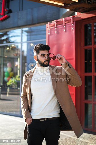 Portrait of fashionable well dressed bearded man at street. Young Indian man in brown coat posing outdoors looking away.
