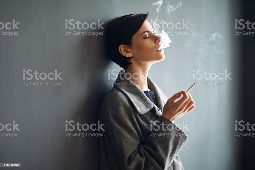 Portrait of fashionable woman smoking a cigarette on dark backgr stock photo