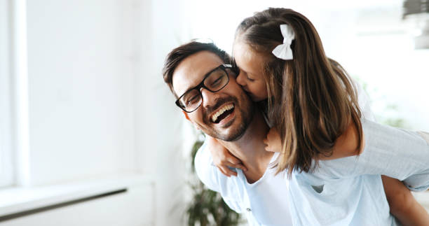 portrait of father and daughter playing at home - daughter stock photos and pictures