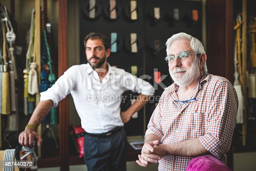 Mature man with his son in their artisanal handicraft traditional textile factory