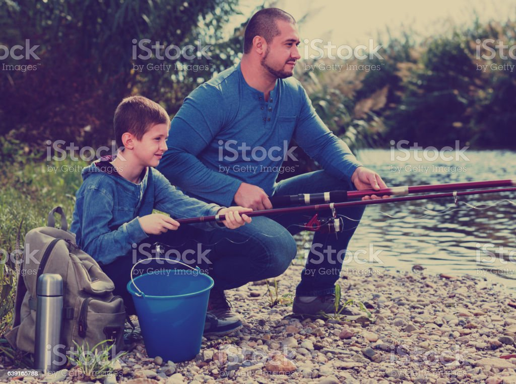 Portrait of father and son fishing with rods stock photo