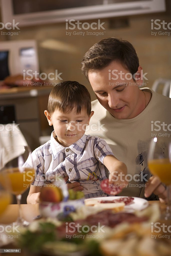 Portrait of Father and Son Sitting at Table royalty-free stock photo