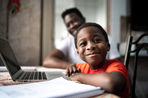 Portrait of father and son studying with laptop on a online class at home