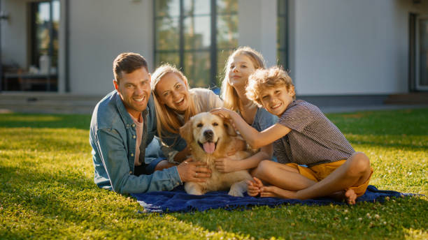 Portrait of Father, Mother and Son Having Picnic on the Lawn, Posing with Happy Golden Retriever Dog. Idyllic Family Have Fun with Loyal Pedigree Dog Outdoors in Summer House Backyard. stock photo