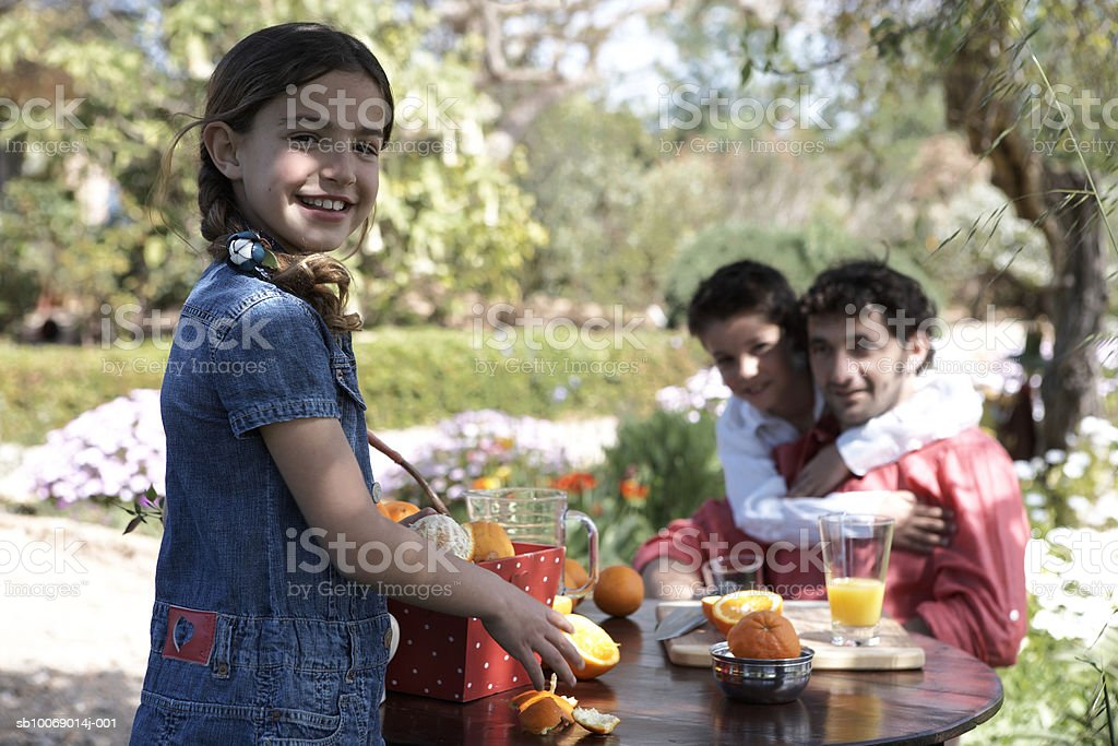 Portrait of father with two children (8-9) in garden, focus on foreground 免版稅 stock photo