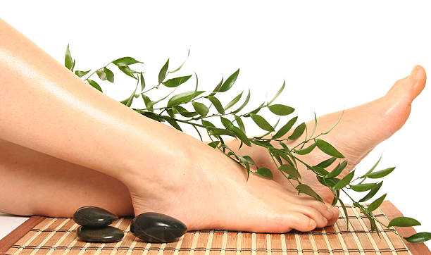 Portrait of feet with massage stones and foliage on bamboo stock photo