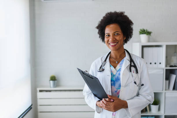 Portrait of female African American doctor standing in her office at clinic Portrait of female African American doctor standing in her office at clinic female doctor stock pictures, royalty-free photos & images