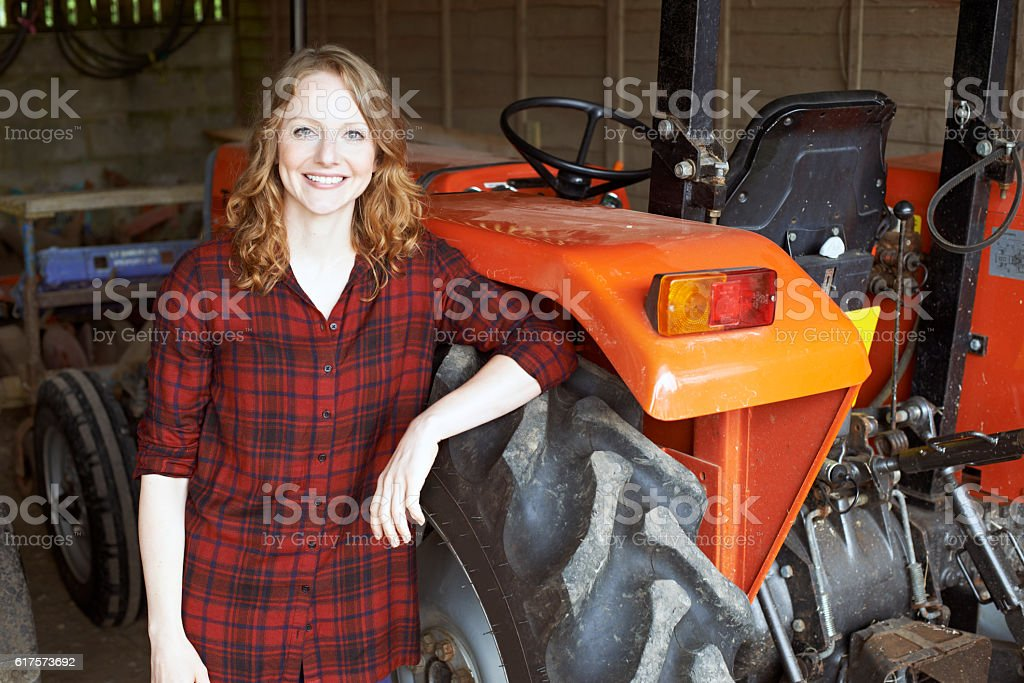Portrait Of Female Agricultural Worker With Tractor - Photo