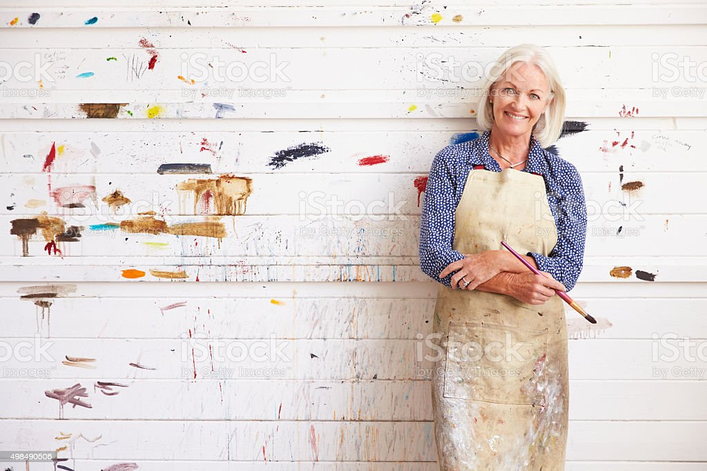 Portrait Of Female Artist Against Paint Covered Wall stock photo
