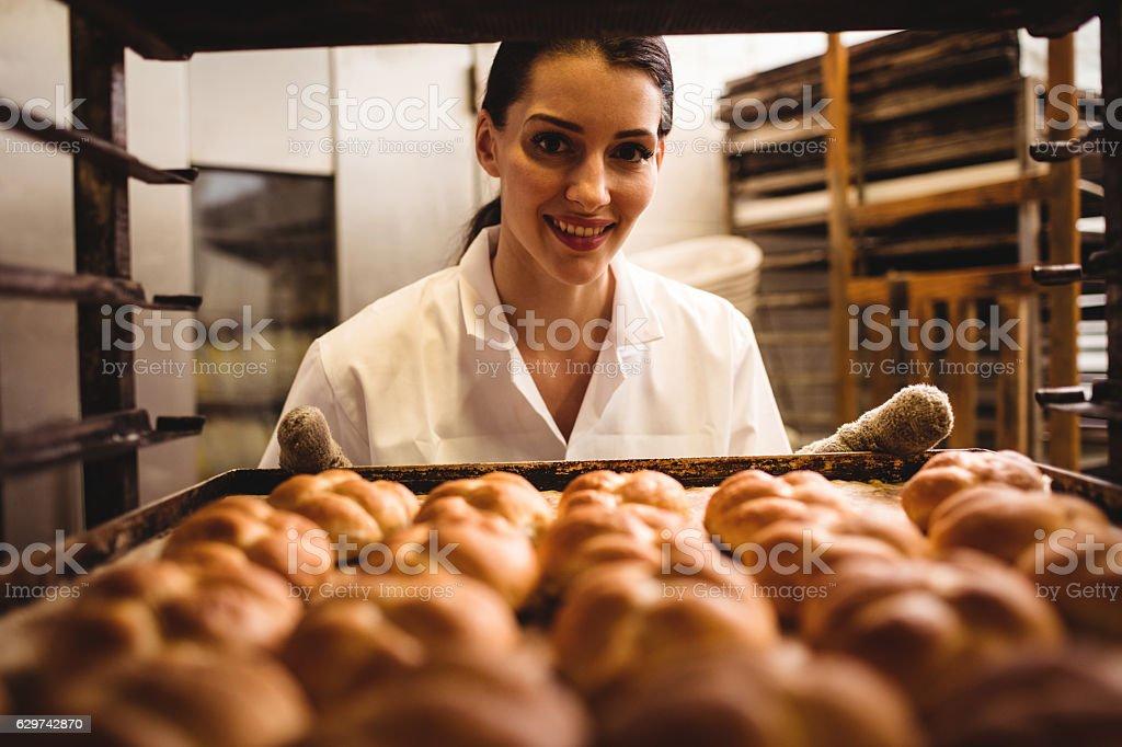 Portrait of female baker holding a tray of michetta stock photo