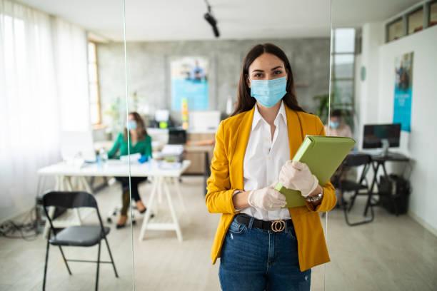 Porträt einer Bankmanagerin mit schützender Gesichtsmaske im Büro – Foto