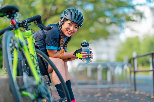 A portrait of a female biker smiling for the camera in a public park.