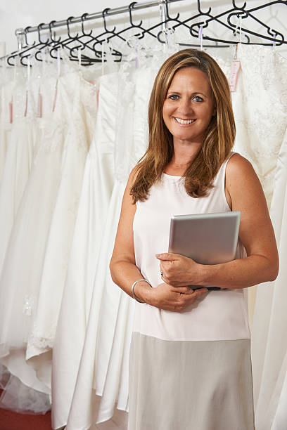 porträt von weiblichen hochzeits-shop-besitzer mit digitalen tablet - hochzeitskleider online stock-fotos und bilder