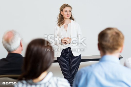 Portrait of young female businesswoman standing in conference room and listening to question. Business presentation concept