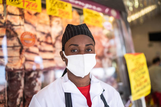 portrait of female butcher working at butcher's shop - with face mask - servizi essenziali foto e immagini stock