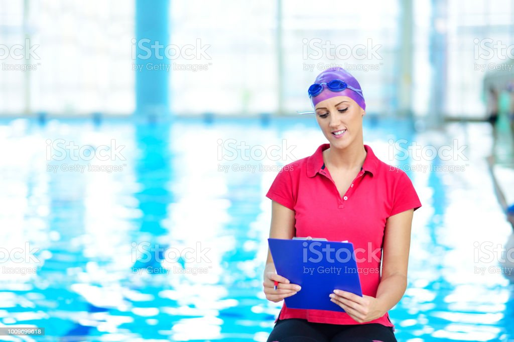 Portrait of female coach with a stop watch and clipboard by pool at...