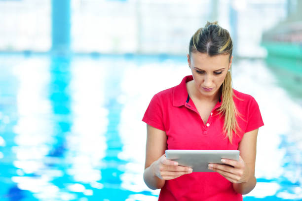 porträt von weiblichen trainer mit stoppuhr und zwischenablage pool am freizeitzentrum - nachrichten video stock-fotos und bilder