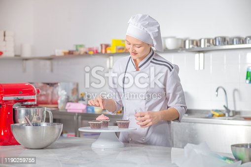 Portrait of female confectioner topping a cupcake with cream