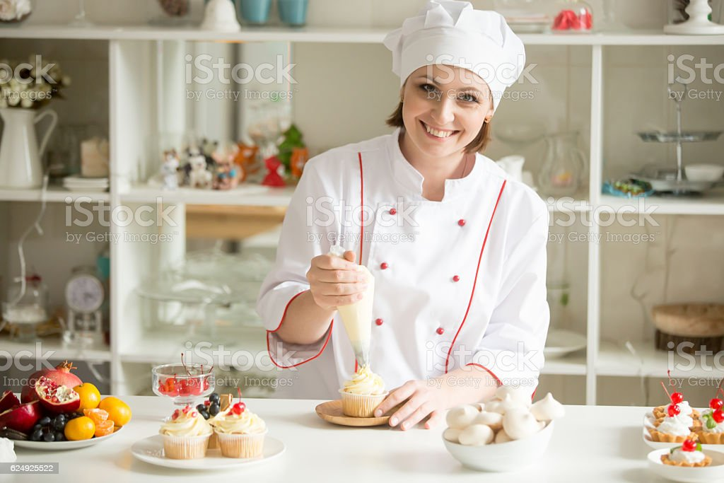 Portrait of female confectioner topping a cupcake with cream - Photo