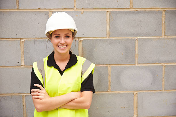 Portrait Of Female Construction Worker On Building Site Portrait Of Female Construction Worker On Building Site reflective clothing stock pictures, royalty-free photos & images