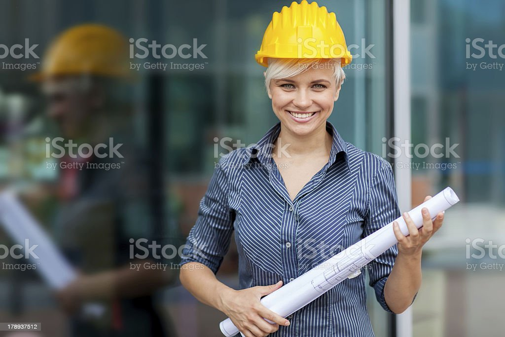 Portrait of female constructor with blueprints stock photo