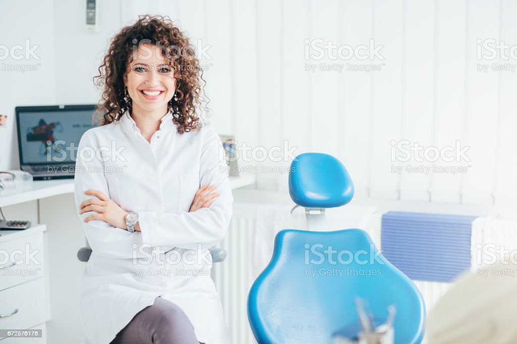 Portrait of female dentist. She standing at her office and she has beautiful smile. stock photo