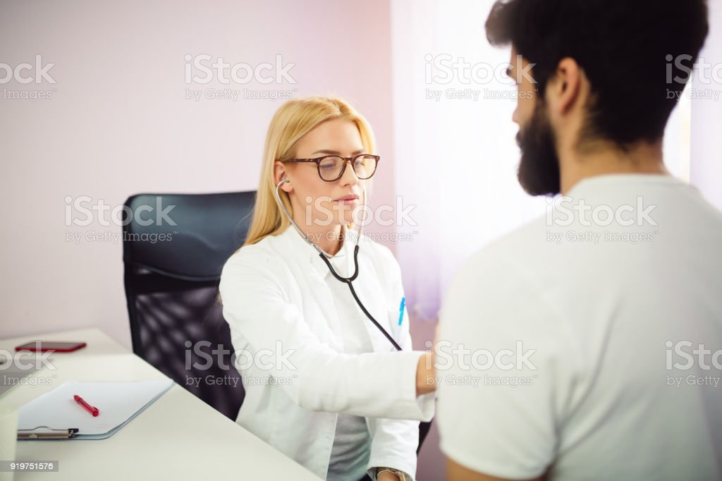 Portrait of female doctor examines a patient with stethoscope. stock photo