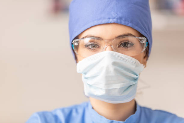 Portrait of female doctor in special surgical sterile protective clothing. Portrait of female doctor in special surgical sterile protective clothing. protective workwear stock pictures, royalty-free photos & images