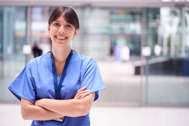 Portrait Of Female Doctor Wearing Scrubs Standing In Modern Hospital Building stock photo