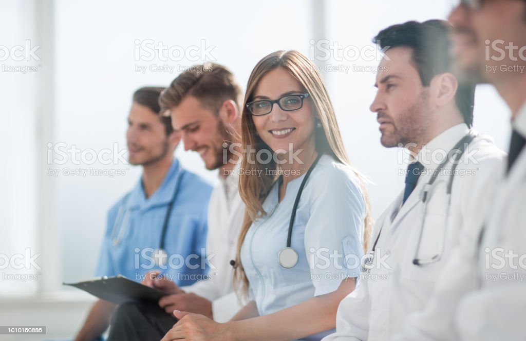 Portrait of female doctor with colleagues at meeting stock photo