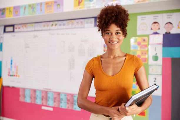 Portrait Of Female Elementary School Teacher Standing In Classroom stock photo