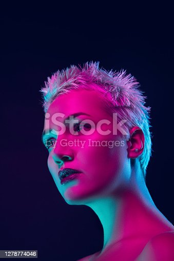 Future. Portrait of female fashion model in neon light on dark studio background. Beautiful caucasian woman with trendy make-up and well-kept skin. Vivid style, beauty concept. Close up. Copyspace