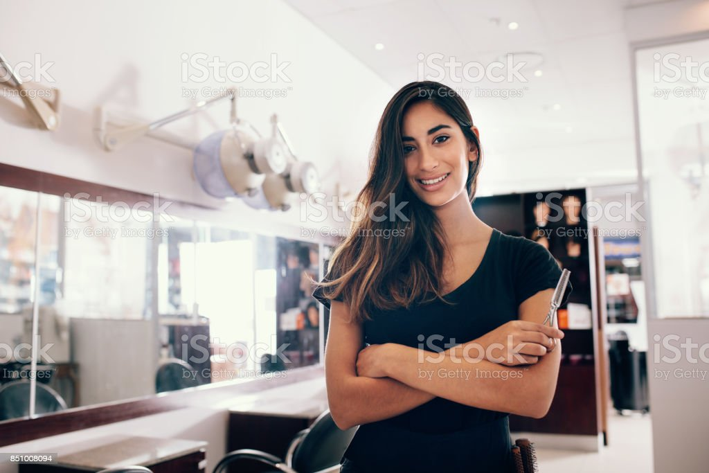 Portrait of female hairdresser standing at salon stock photo