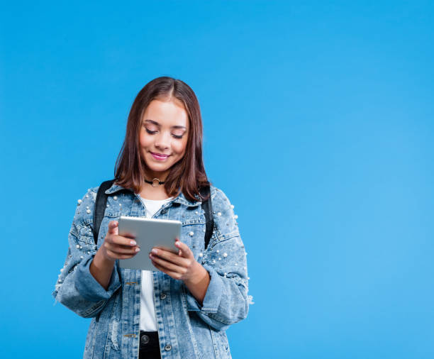 portret van vrouwelijke middelbare schoolstudent die digitale tablet gebruikt - zwarte spijkerbroek stockfoto's en -beelden