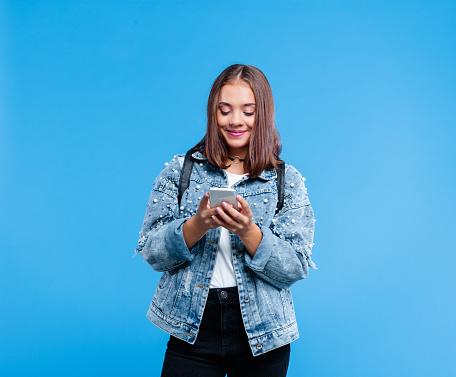 Portrait of female high school student using smart phone